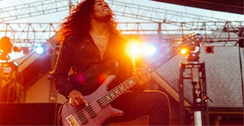 artist, Skylar Accord, playing electric bass in concert