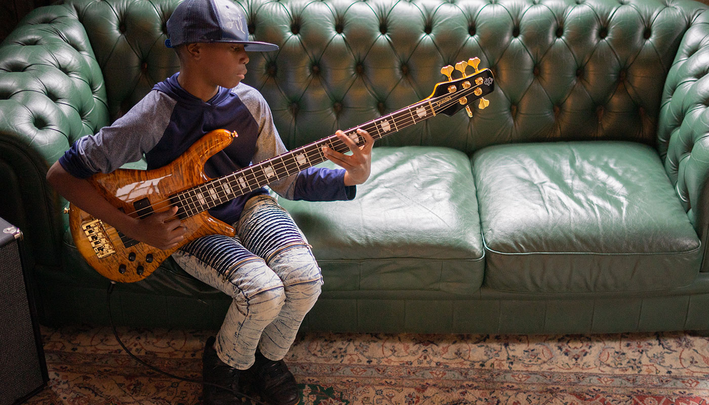 Teen boy wearing purple and playing a Spector bass and sitting on a vintage leather couch