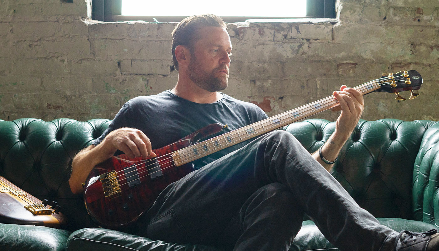 Man playing a Spector bass and sitting on a vintage leather couch in front of a worn concrete wall