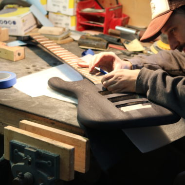 man making bass in workshop