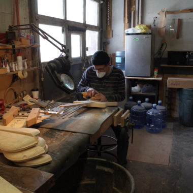 man making electric basses in workshop