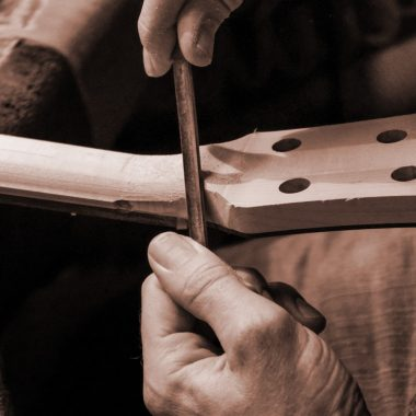 hands using tool to cut wood into headstock