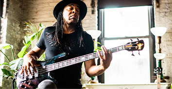 artist, Doug Wimbish, playing Spector bass inside brick building