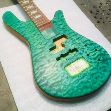 closeup of body of green Spector bass