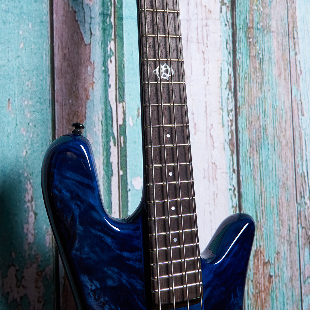 top of blue Spector bass body in front of blue wood panels