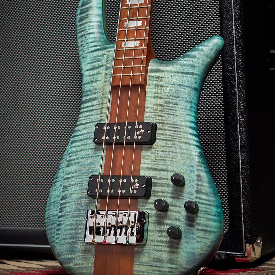 close up of Euro RST bass guitar body in Turquoise Tide matte finish leaned against a black amp